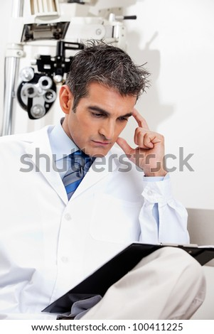 Serious male optometrist reading a document with concentration at his clinic - stock photo