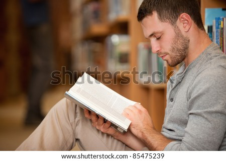 Serious male student reading a book in a library - stock photo