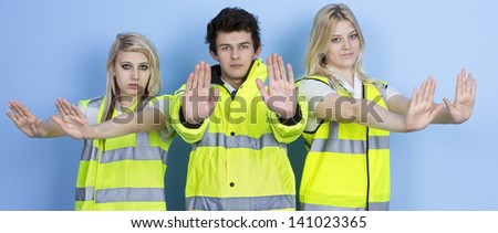 Serious Man And Woman Wearing High-visibility Jacket Showing Stop Sign