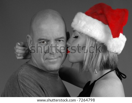Serious Man Being Kissed on Cheek by Pretty Woman in Santa Hat - stock photo