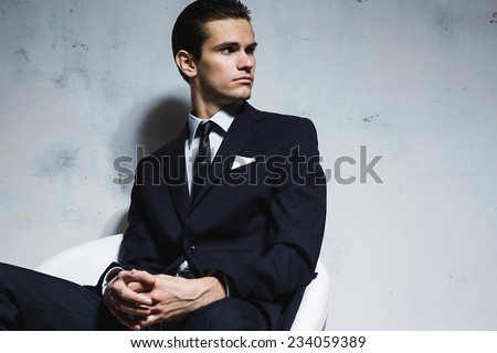 Serious man in a black business suit sitting on a white chair on a white grungy background. Studio shoot  - stock photo