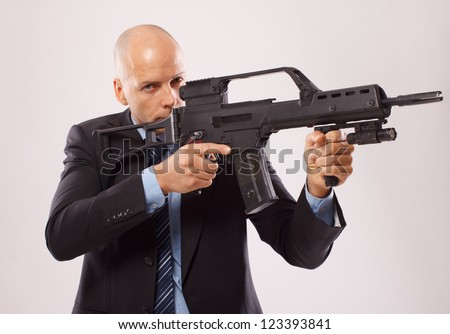 Serious man in a suit holding a rifle isolated on a white
