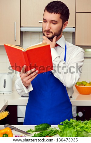 serious man in blue apron reading cookbook