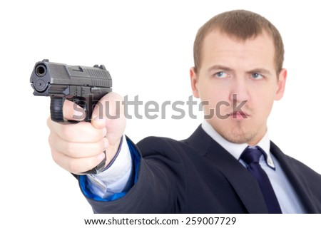 serious man in business suit shooting with handgun isolated on white background - stock photo