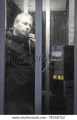 Serious man in public telephone booth at night