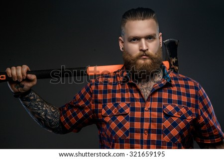 Serious man in red t shirt holding big axe. Isolated on grey background. - stock photo