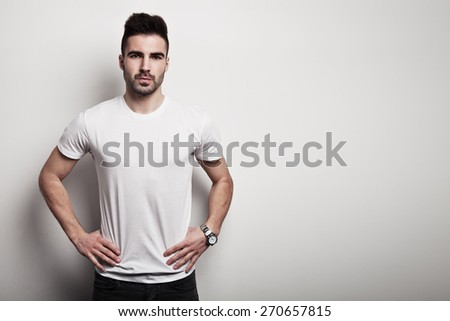 Serious man in white blank t-shirt, white wall background - stock photo