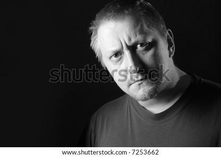 Serious man looking at camera over dark background with space for text on left. Black and white image.