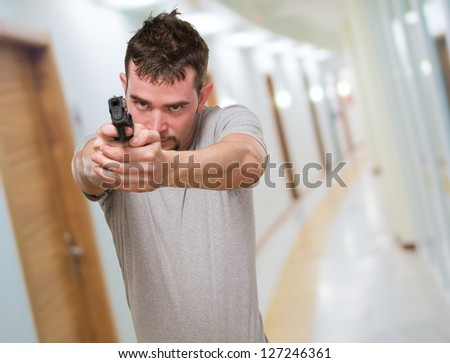 serious man pointing with gun, indoor