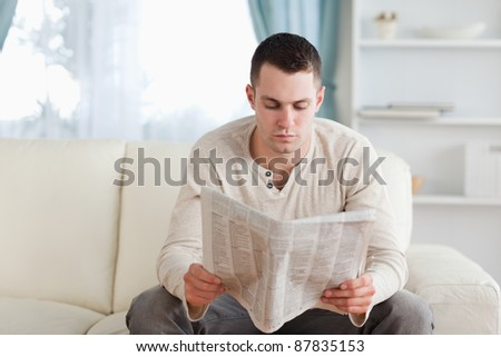 Serious man reading a newspaper in his living room