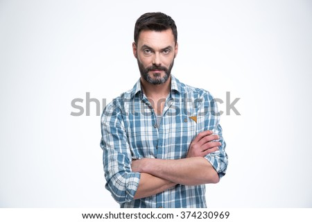 Serious man with arms folded standing isolated on a white background and looking at camera - stock photo