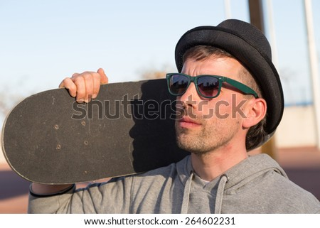 Serious man with his skateboard on a spring afternoon - stock photo