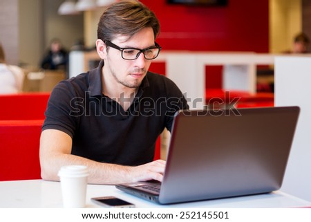 serious man with laptop in cafe - stock photo