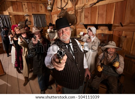 Serious man with old west gang holding guns - stock photo