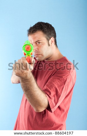 Serious man with toy gun pointing at camera - stock photo