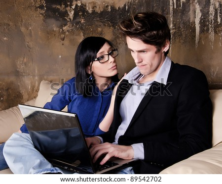 Serious man working on her laptop while her girlfriend is worry - stock photo