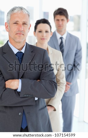 Serious manager crossing his arms in front of his young business team - stock photo