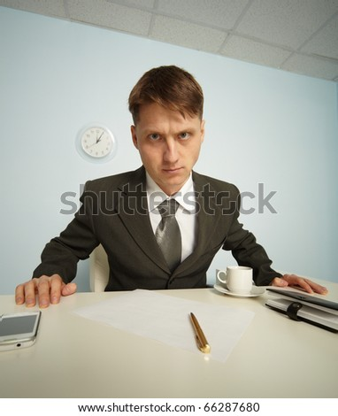 Serious manager strictly looking from his workplace - stock photo