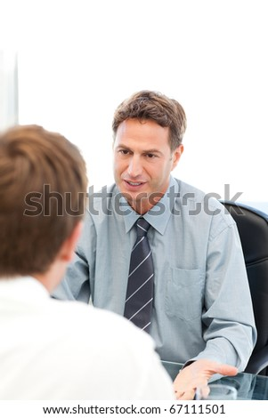 Serious manager talking with an employee during an interview at the office