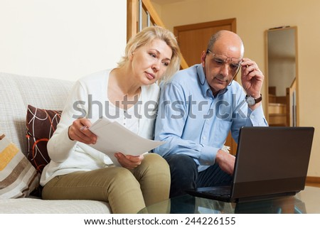 Serious mature man and woman reading finance documents in home interior - stock photo