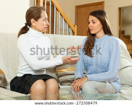 Serious mature mother and  daughter  talking in home interior