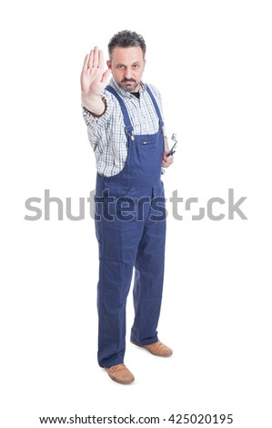 Serious mechanic in overalls making a stop gesture while holding spanner isolated on white background - stock photo