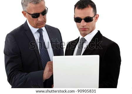 Serious men in smart suits with sunglasses holding a laptop - stock photo
