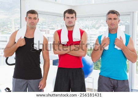 Serious men looking at camera in fitness studio - stock photo