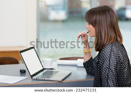 Serious Middle Age Businesswoman Checking Sales at Laptop on Table While Having a Cup of Coffee on Side. Captured Indoor. - stock photo