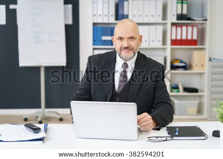 Serious middle-aged business manager sitting at his desk in the office working on a laptop computer looking at the camera with a pensive expression