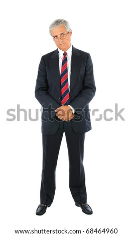 Serious middle aged businessman in a suit and tie standing with hands clasped in front peering over the top of his glasses. Full length over a white background. - stock photo