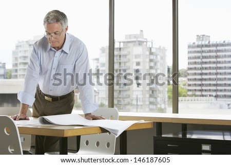 Serious middle aged businessman leaning on desk in office - stock photo