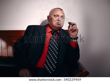 Serious middle aged businessman wearing black suit, red shirt and wristwatch sitting on old fashioned sofa in office and smoking cigar - stock photo