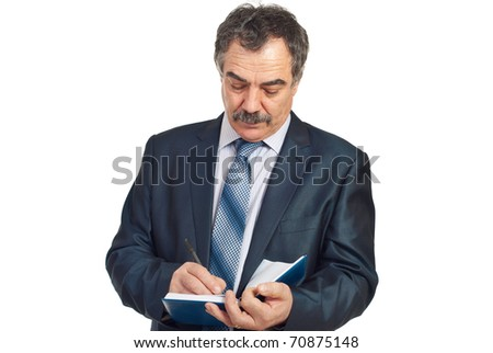 Serious middle aged corporate man writing in personal agenda isolated on white background