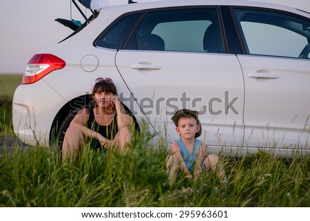 Serious Mom with is Cute Son Sitting Beside their White Car While Waiting for Something. - stock photo