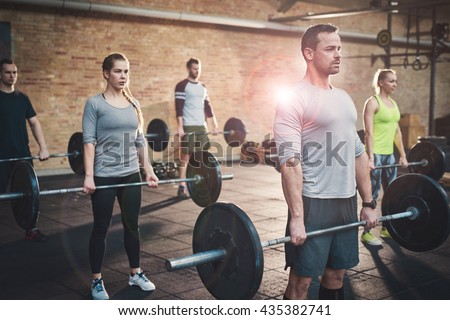 Serious muscular bearded man in shorts and gray tee shirt leading small group of young adults in barbell exercises for fitness training - stock photo