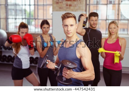 Serious muscular man holding dumbbells with group using other exercise equipment objects in background at gym with large windows - stock photo