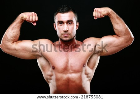 Serious muscular man showing his biceps on black background - stock photo