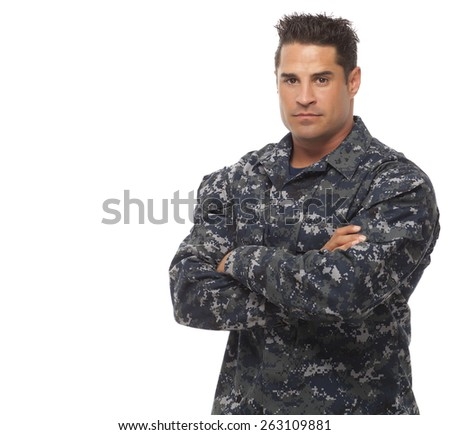 Serious navy man posing with arms crossed against white background - stock photo