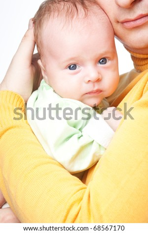 Serious newborn baby looking at camera while father hugging it and holding in his hands isolated over white background. Happy father likes his son. - stock photo