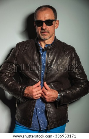 serious old casual man pulling his jacket's collar , standing against studio wall
