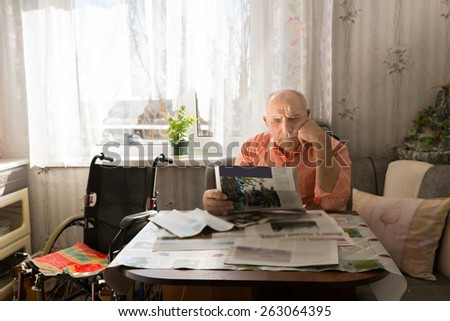 Serious Old Man Reading News on Tabloids Seriously While Resting at the Living Room with his Wheel Chair on the Side. - stock photo
