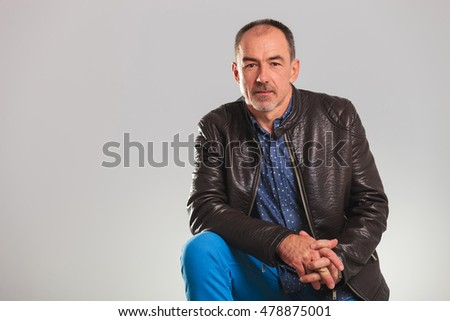 serious old man sitting in studio, on grey background