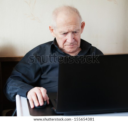 serious old man working on a computer - stock photo