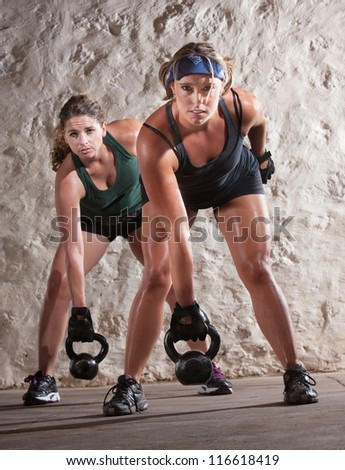 Serious pair of young women lifting weights during boot camp workout - stock photo