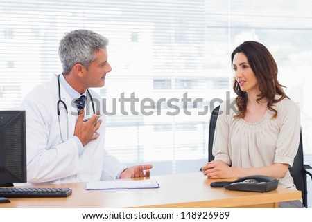 Serious patient talking with her doctor about illness in medical office - stock photo