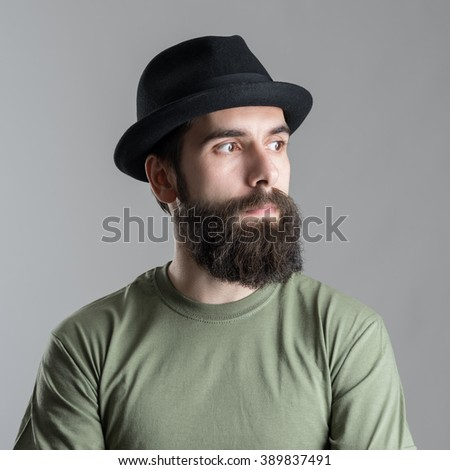 Serious pensive bearded man looking away.  Headshot close up portrait over gray studio background.  - stock photo