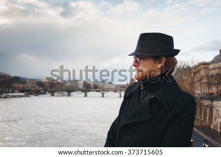 Serious Pensive Bearded Man Wearing Hat in Paris, France, Walking near Seine River. Headshot Composition, Space for Text. - stock photo