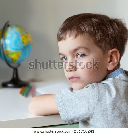 Serious pensive pupil sits at desk, writing in notebook, class, indoor - stock photo