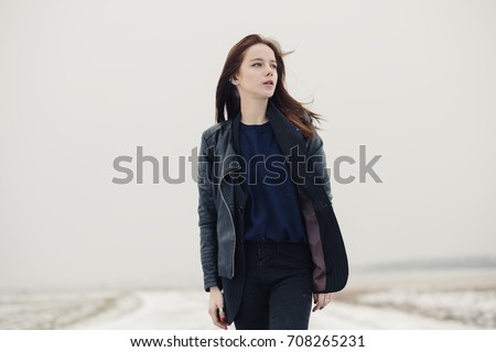 serious pensive young beautiful girl stands in winter outdoors